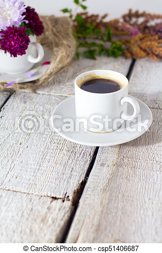 Romantic background with cup of coffee, flowers over white table. - csp51406687