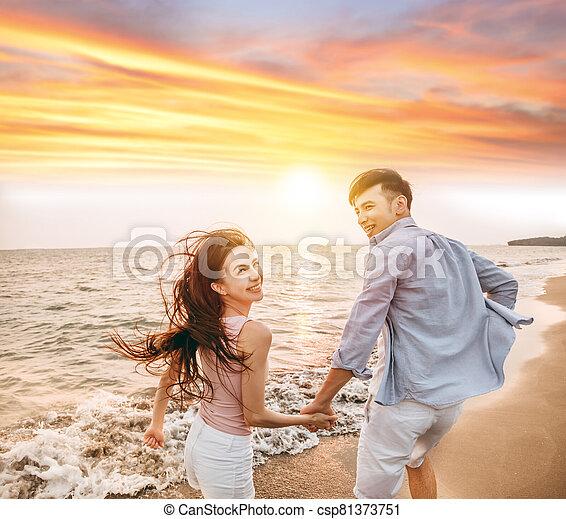 Romantic couple having fun on the beach at sunset - csp81373751