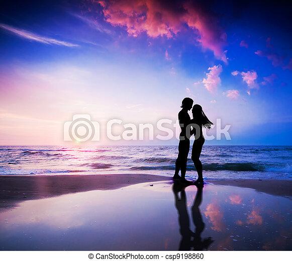 Romantic couple on beach at sunset - csp9198860