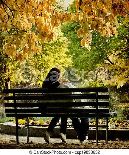 Romantic couple sitting in the autumn park - csp19833652
