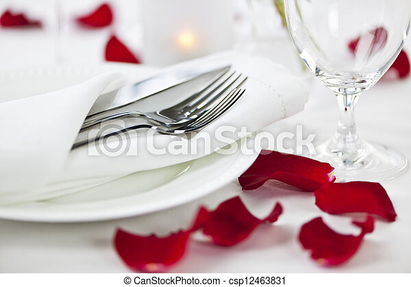 Romantic dinner setting with rose petals - csp12463831