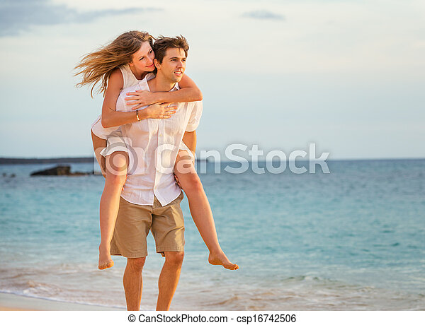 Romantic happy couple on the beach at sunset, man and woman in love - csp16742506