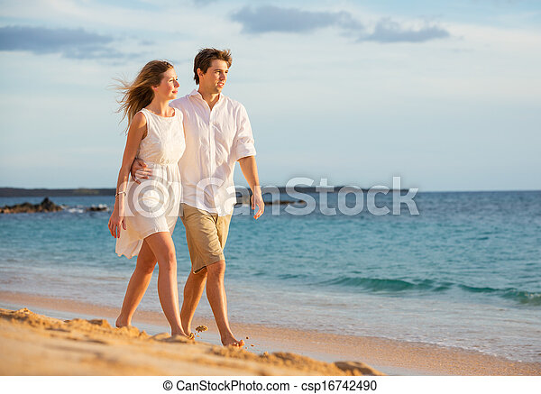 Romantic happy couple walking on beach at sunset. Smiling with arms around each other. Man and woman in love - csp16742490