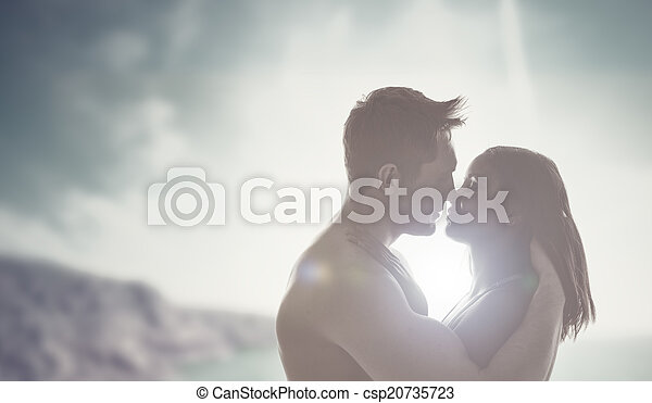 Romantic kiss backlit by the sun - csp20735723