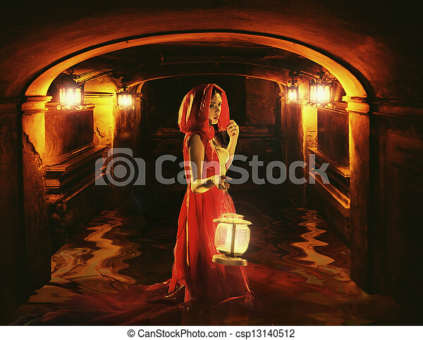 Romantic lady holding a lantern in a dark dungeon - csp13140512