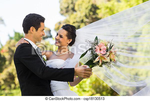 Romantic newlywed couple dancing in park - csp18130513