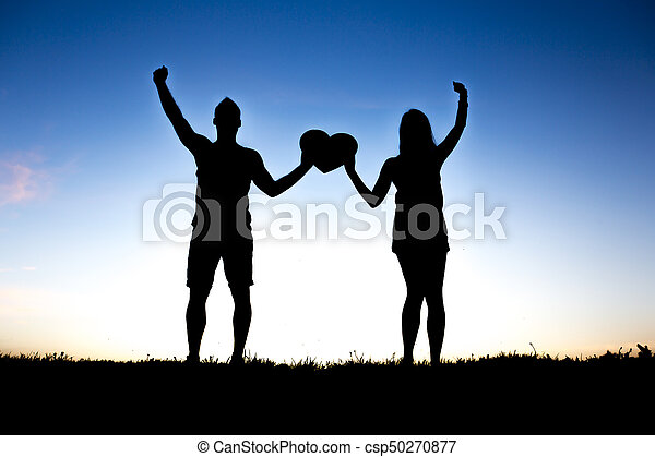 Romantic young couple holding heart shape on hands at sunset - csp50270877