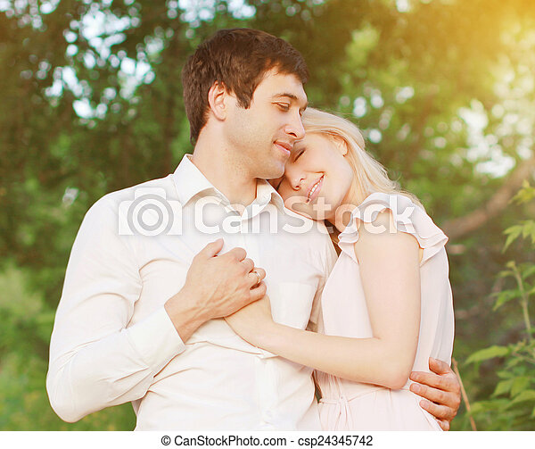 Romantic young couple in love outdoors, warm tender feelings - csp24345742