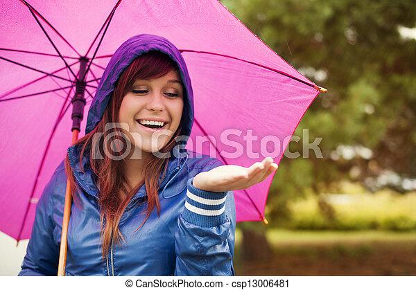 Mujer alegre bajo paraguas rosa, buscando lluvia - csp13006481