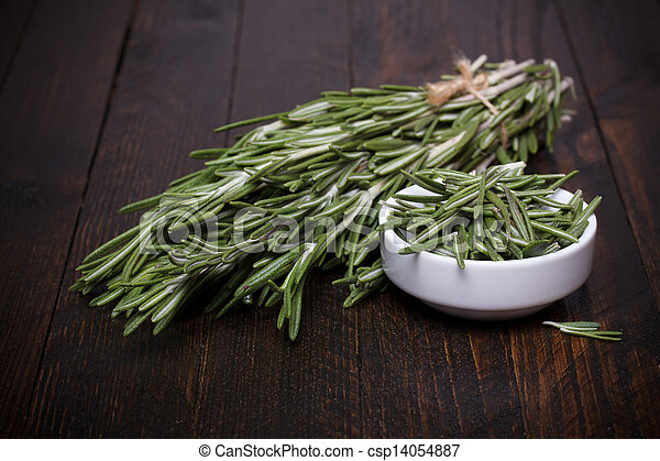 Rosemary bunch and bowl on rustic wooden table still life - csp14054887