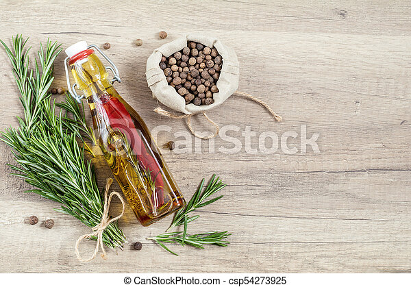 Rosemary bunch of bouquets, olive oil with pepper and spices, fragrant pepper on light wooden surface. Top view, copy space. - csp54273925