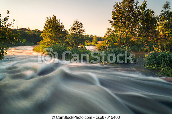 Rough river with fast-flowing in the fog and mist on the background - csp87615400