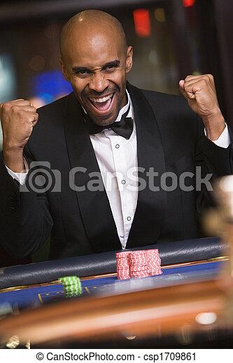 Ein Mann im Casino gewinnt Roulette und lächelt (wählter Fokus) - csp1709861