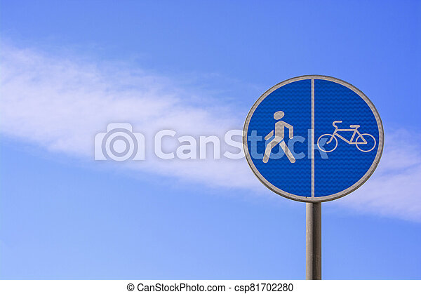 Round blue sign Pedestrian and bicycle path with combined path on the background of a beautiful cloudy sky - csp81702280