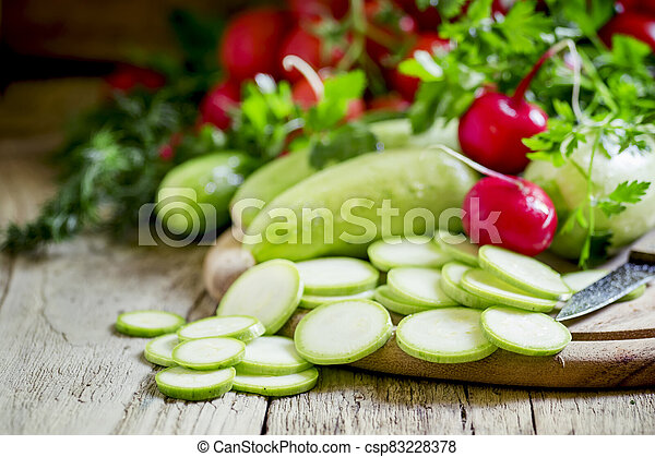 Round zucchini slices and fresh radish, vintage wooden background, selective focus, shallow depth of field - csp83228378