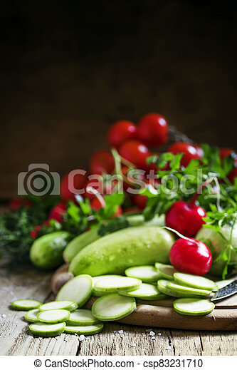 Round zucchini slices and fresh radish, vintage wooden background, selective focus, shallow depth of field - csp83231710