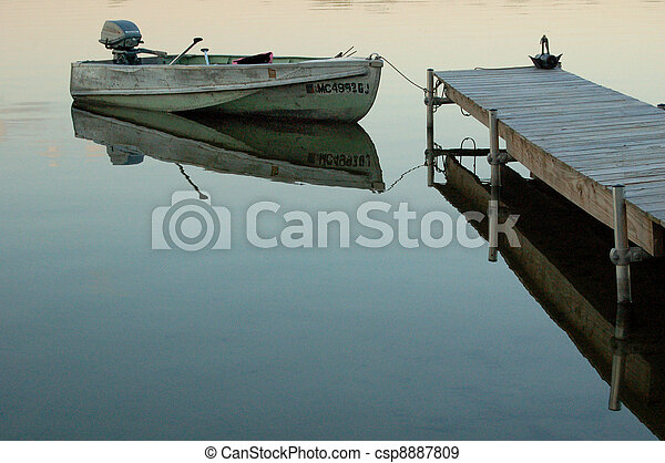 Row boat at dock. Old row boat with motor tied up to wooden dock in calm water in an inland lake.
