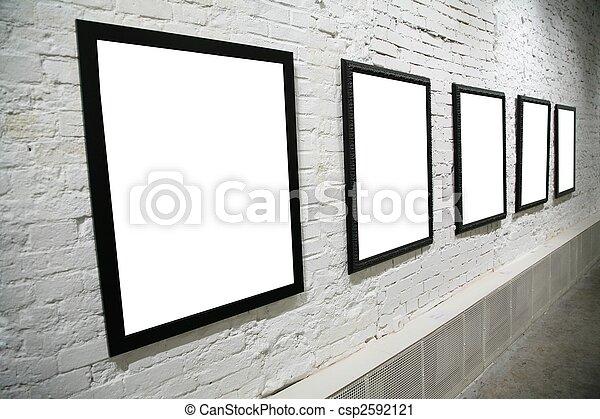 row of black frames on white brick wall - csp2592121