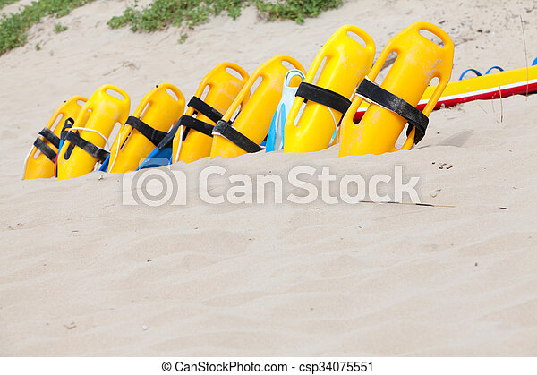 Row of lifesaving floatation devices on the beach - csp34075551