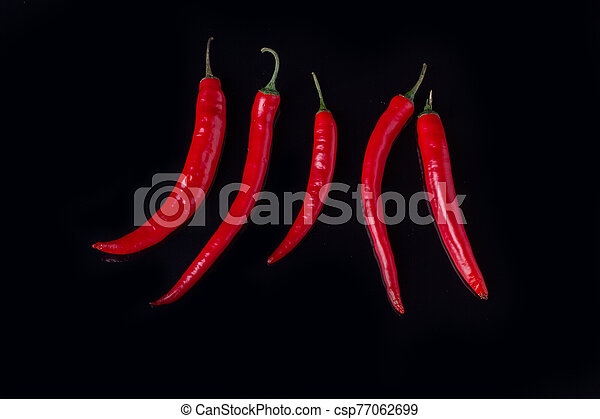 Row of red hot chili peppers on black background. - csp77062699