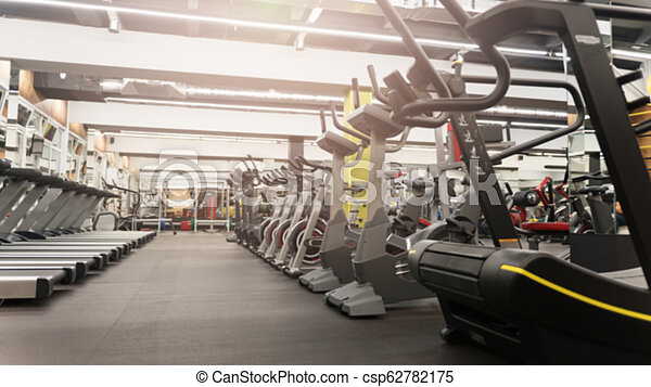 Row of treadmills in big new gym without people - csp62782175