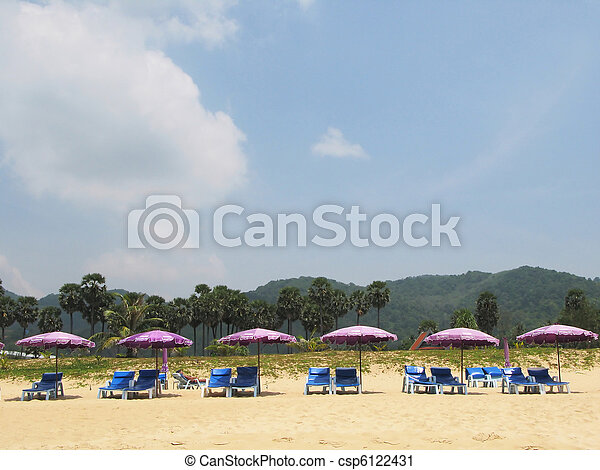 Row Of Umbrellas And Sunbeds At A Tropical Beach