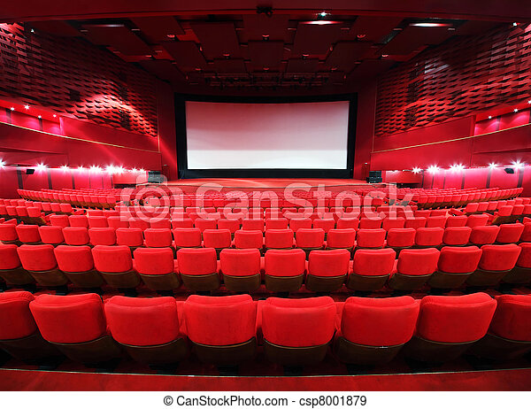 Rows of comfortable red chairs towards to big screen in illuminate red room cinema  - csp8001879