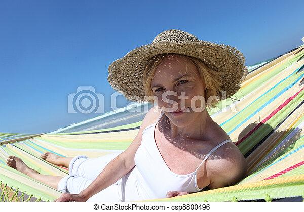 Mujer rubia descansando en la playa en Hammock - csp8800496