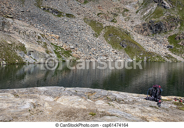 rucksack on a rock at a lake - csp61474164