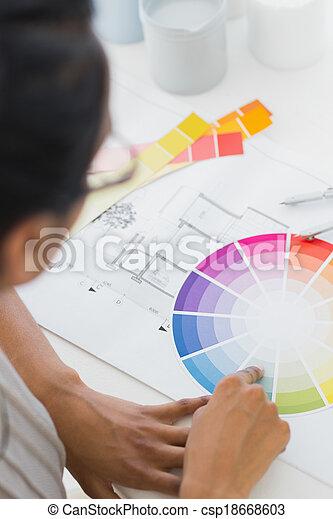 Diseñadora de interiores mirando la rueda de colores en su escritorio - csp18668603
