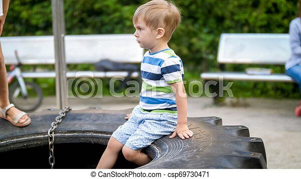 Retrato de adorable niño de 3 años sentado en el patio en una rueda de goma - csp69730471