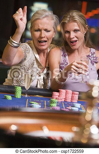 Dos mujeres en el casino jugando a la ruleta y sonriendo - csp1722559