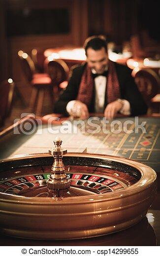 Hombre de traje y bufanda jugando a la ruleta en un casino - csp14299655