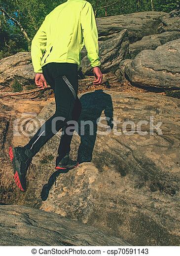 Runner in yellow green shinning jacket and black leggings - csp70591143