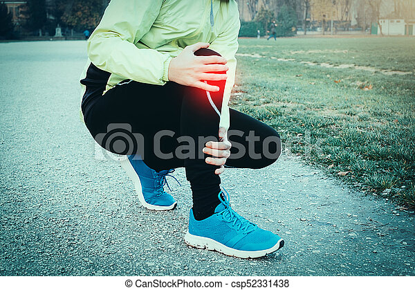 Runner with injured ankle while training in the city park in col - csp52331438