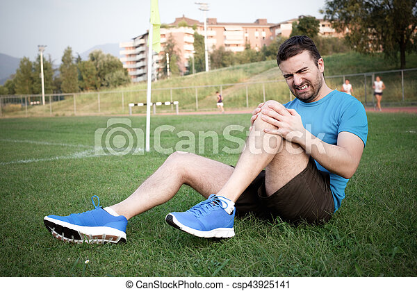 Runner with injured knee on the grass - csp43925141