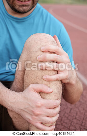 Runner with injured knee on the track - csp40184624