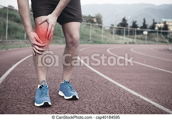 Runner with injured knee on the track - csp40184595