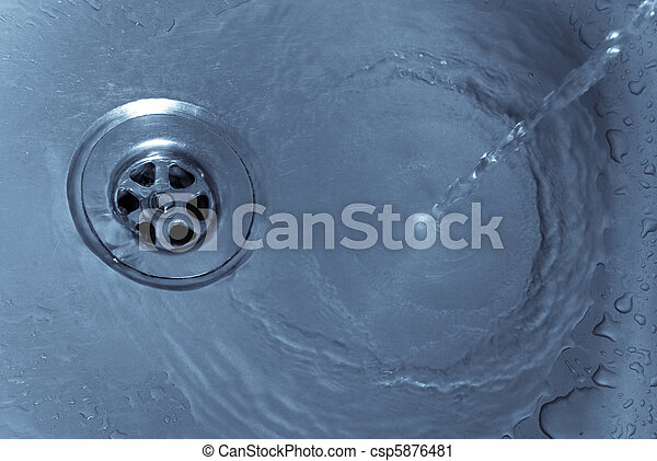 Running water drains down a stainless steel sink - csp5876481