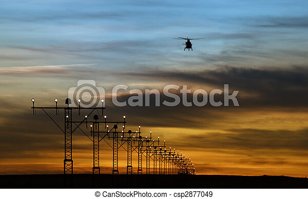 runway lights and silhouette of a helicopter - csp2877049