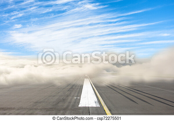 Runway road wrapped in dense low fog, clear blue sky from above. The concept of bad weather at the airport, the delay in the schedule of transport. - csp72275501
