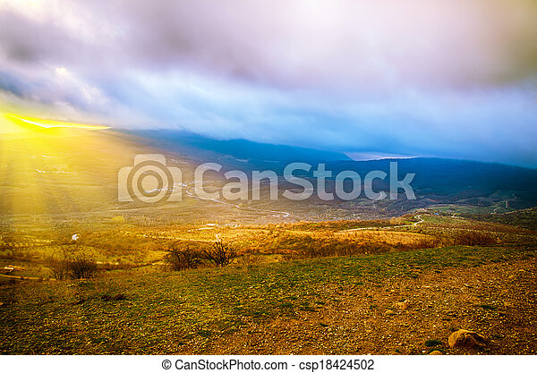 Rural sunset landscape with green hills, dramatic sky, mountains and sun rays