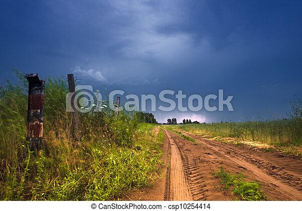 Rural road and dark storm clouds - csp10254414