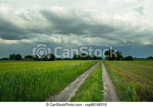 Rural road through green fields and rainy clouds on sky - csp86169318