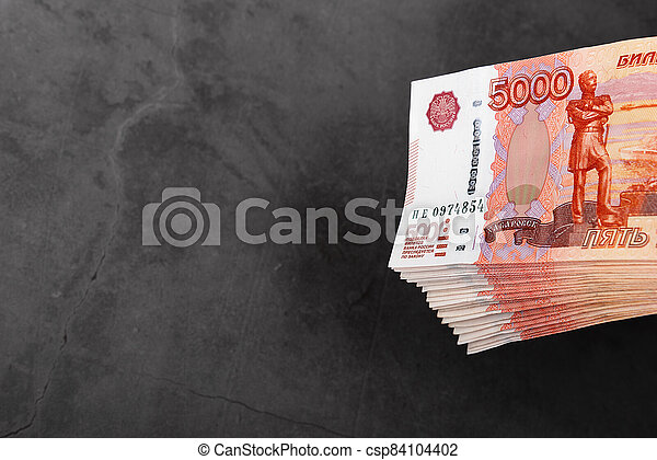Russian cash banknotes of five thousand rubles, the bundle hangs on a gray background. - csp84104402