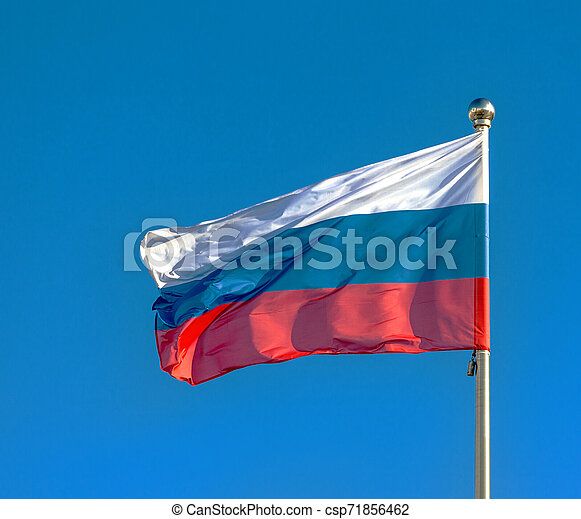 Russian flag on a background blue sky. - csp71856462