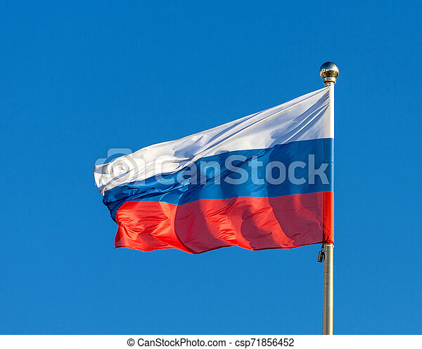 Russian flag on a background blue sky. - csp71856452