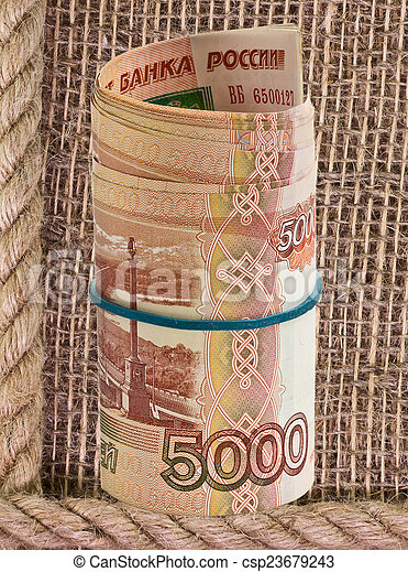 Russian rubles rolled into a tube on a background of burlap - csp23679243