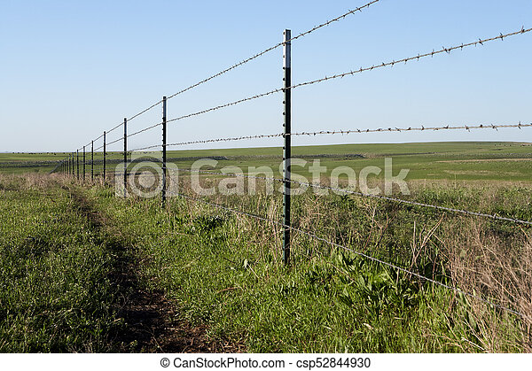 Rustic Fence On A Farm With Barbed Wire Strands