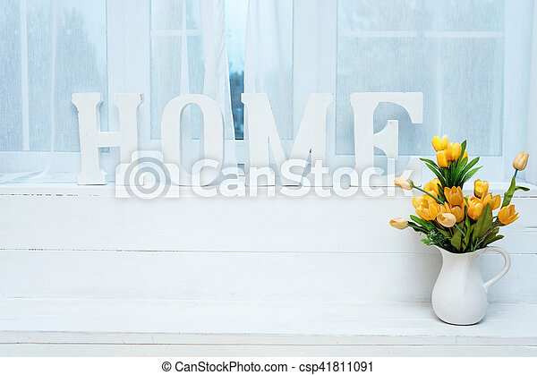 Rustic interior decor. Word Home on windowsill with white jug full of yellow tulips. - csp41811091